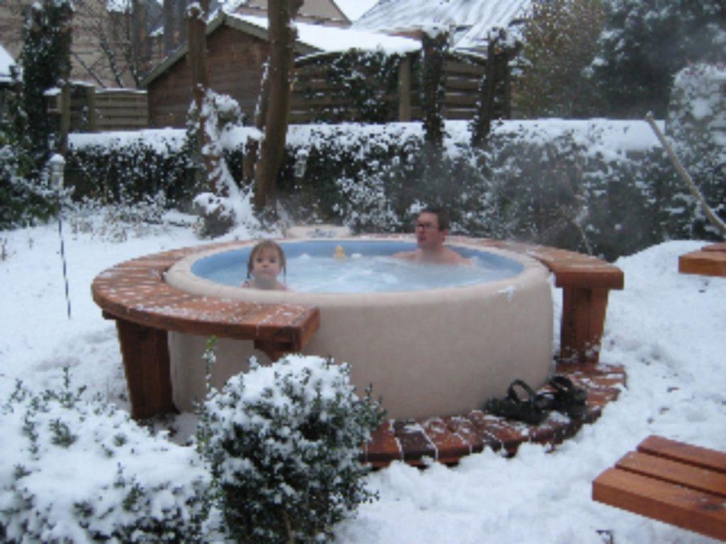 Un homme et une petit fille profite de leur spa softub en hiver