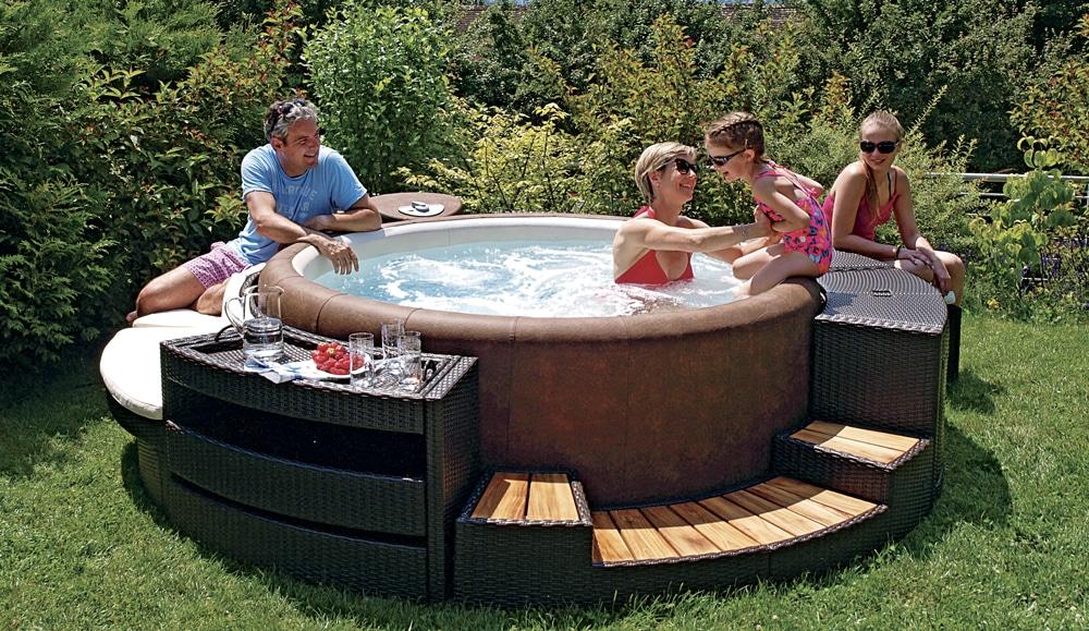 Une famille joue dans le spa en dur, Softub et une petite fille est assise sur le spa
